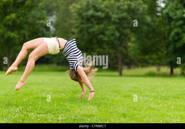 Young sporty girl jump backwards at the park, image with narrow depth of field - Stock Image