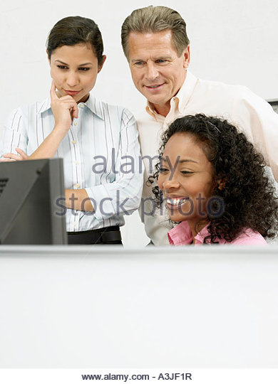 Colleagues looking at computer screen - Stock Image