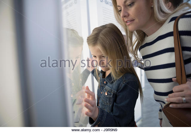 Curious mother and daughter looking at exhibit in museum - Stock Image