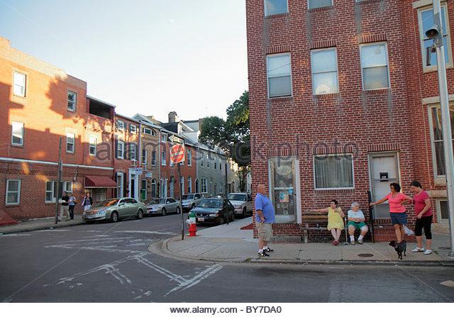 Baltimore Maryland Little Italy ethnic neighborhood community row house brick man woman neighbor sit on sidewalk - Stock Image