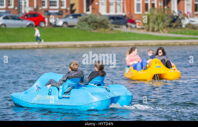 Fun day out. Children in pedalo boats on a Spring day on a boating lake at the Oyster Pond in Littlehampton, West - Stock Image