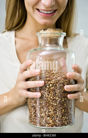 Holding jar of dried lentils - Stock Image
