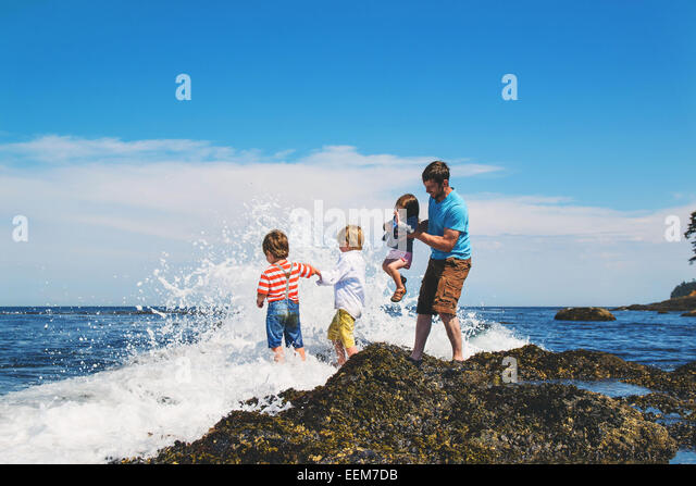 Father and three children (2-3, 4-5) playing in waves - Stock Image