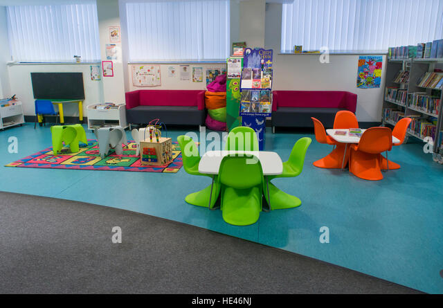 Library interior, West Yorkshire, England - bookshelves with rows of books, tables and chairs in the children's - Stock Image