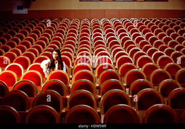portrait of a pretty girl hipster in a movie theater wearing hat, dreaming alone, lifestyle people concept - Stock Image
