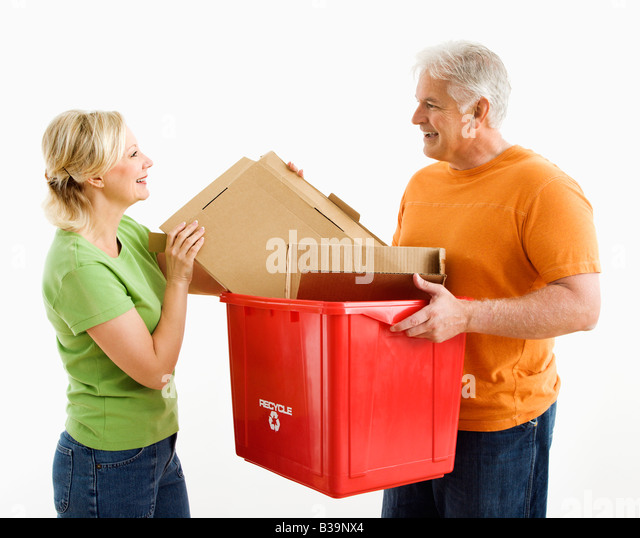 Man holding recycling bin while woman places cardboard into it - Stock Image