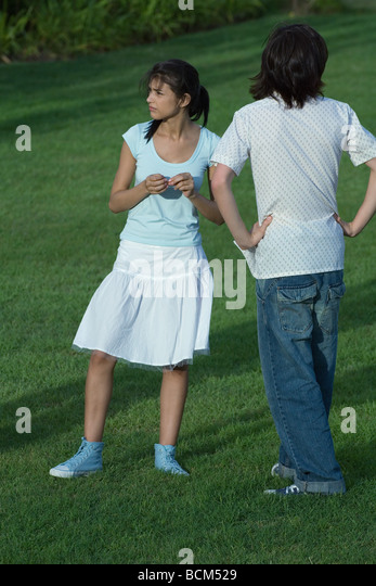 Young couple standing in park, waiting - Stock Image