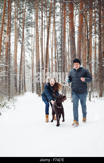 Young Couple with a Dog Having Fun in Winter Forest on Vacations. Selective Focus. Lifestyle of Happy Modern Family. - Stock Image