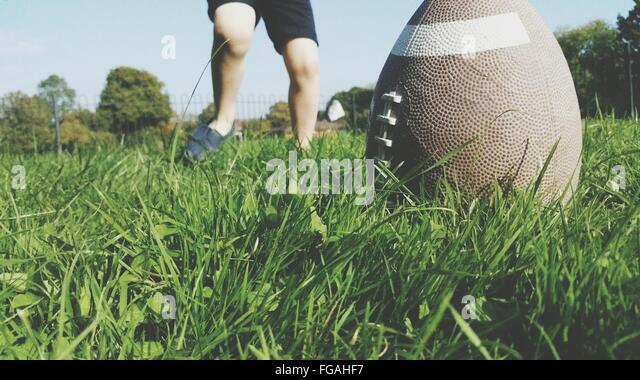 Low Section Of Person Playing With Rugby Ball On Grassy Field - Stock Image