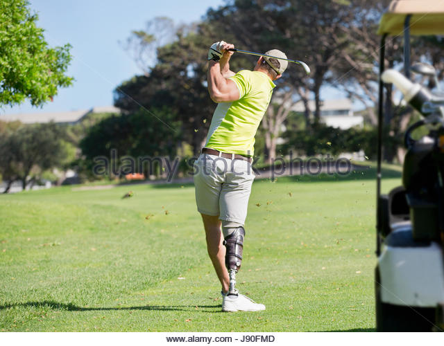 Rear View Of Golfer With Artificial Leg Hitting Ball On Fairway - Stock-Bilder