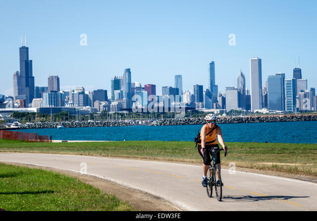 Illinois Chicago South Side Lake Michigan 39th Street Beach Lakefront Trail woman biker bicycle riding city skyline - Stock Image