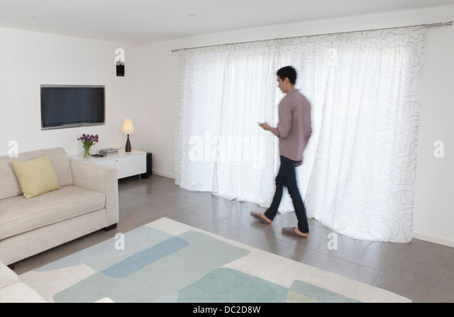 Man with mobile phone walking past curtains - Stock-Bilder