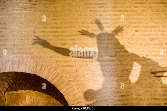 The shadow of a Resurrected Jesus Christ image on a wall of Santa Marina church, Seville, Spain - Stock-Bilder