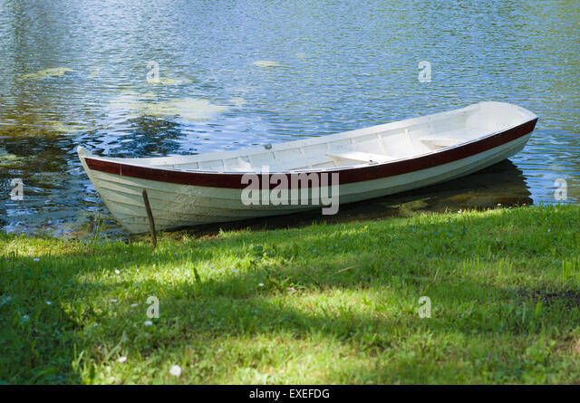 Rowboat at pond shore in summer park - Stock Image