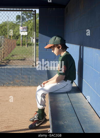 sad boy sitting alone in baseball dugout - Stock Image