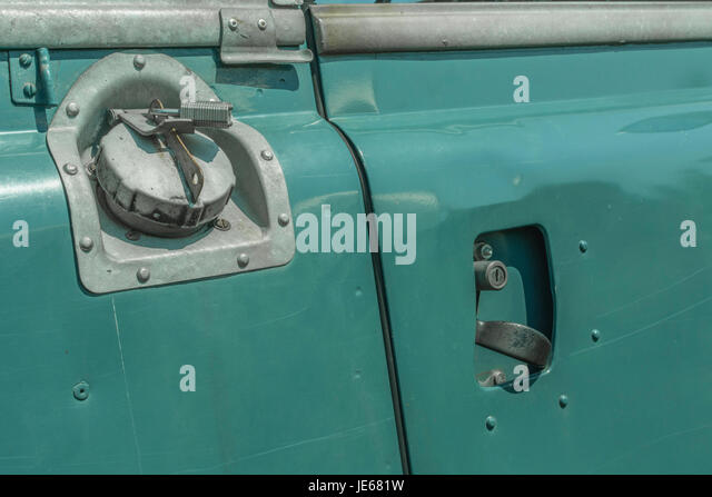 Close-up of fuel tank filler cap and driver side door handle on a Classic Series 2 Land Rover (specifically a Series - Stock Image