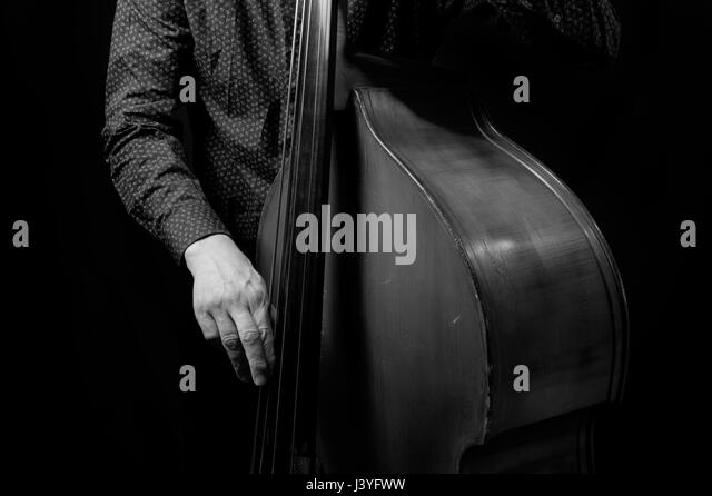 Black and white photograph of a man in playing bass with his face hidden - Stock Image