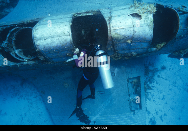 Diver exploring wreck of Douglas Devastator in the Western Pacific at Jaluit Atoll - Stock Image