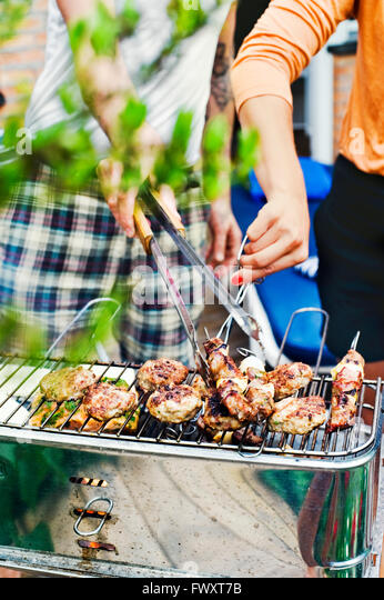 Sweden, Uppland, Danderyd, Couple grilling meat on barbecue - Stock Image