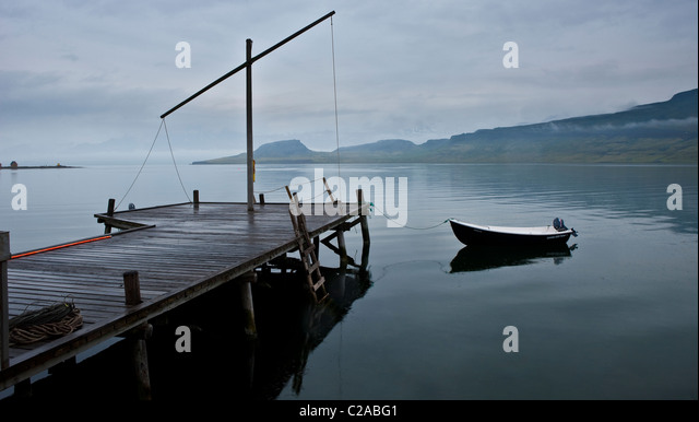 Old wood dock with boat, Eskifjordur, Iceland - Stock Image