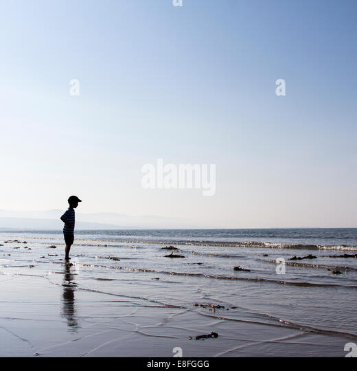 Boy standing on beach looking out to sea - Stock Image