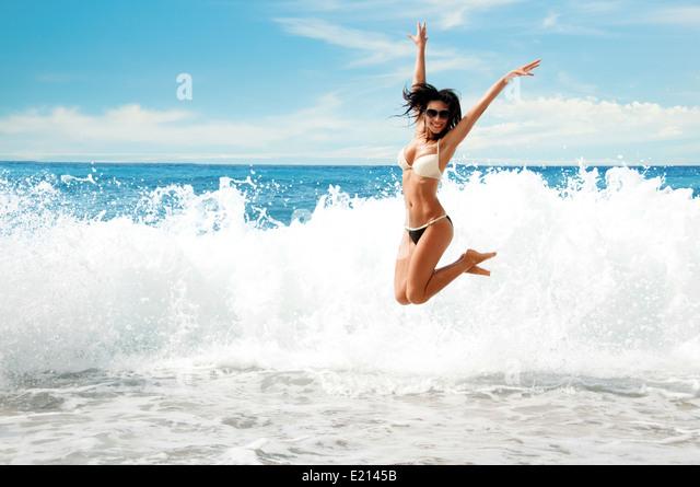 Beautiful young girl jumping on sea - Stock Image