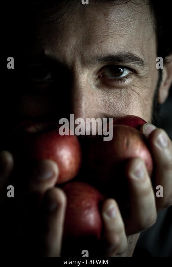 Italy, Lombardy, Milan, Man is holding apples with his hands - Stock Image