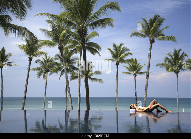 Young woman relaxing by pool with palm trees and the sea beyond - Stock Image