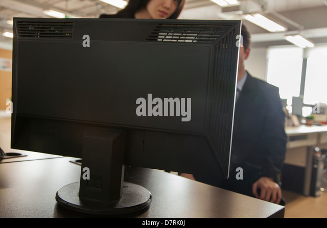 Two coworkers looking at computer monitor - Stock Image