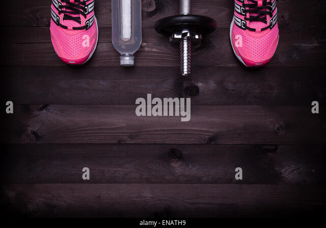 Sport equipment. Sneakers, water and a dumbbell on a black wooden background - Stock-Bilder