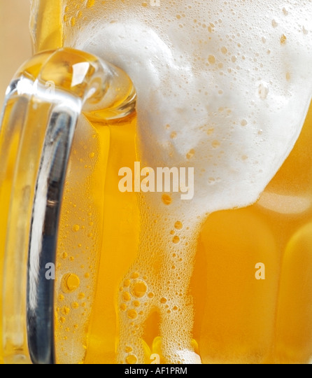 Beer Close Up of a Glass of Cold Draught Beer with Foam Overflowing Down the Sides - Stock Image
