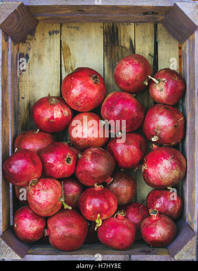 Turkish ripe pomegranates in wooden box, copy space - Stock Image
