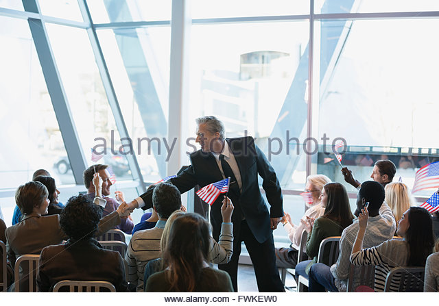 Politician shaking hands with audience at political rally - Stock Image