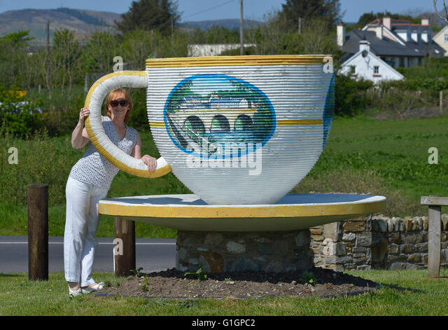 Woman with huge cup and saucer in Ramelton, County Donegal, Ireland. - Stock Image