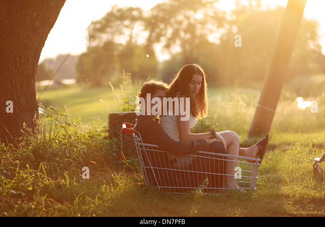 Loving couple sitting in a shopping basket in backlight - Stock Image