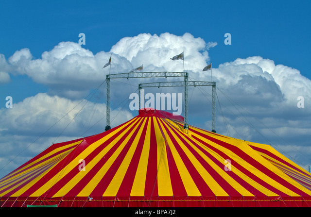 Striped circus tent against a blue sky with fluffy clouds. Horizontal - Stock-Bilder