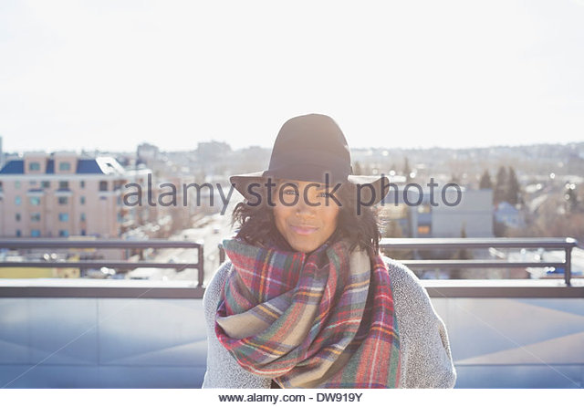 Portrait of woman standing on patio with hat and cozy scarf - Stock Image