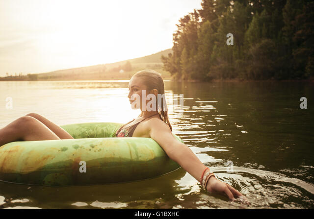 Side portrait of young woman in lake on inflatable ring. Woman relaxing in water on a summer day. - Stock Image