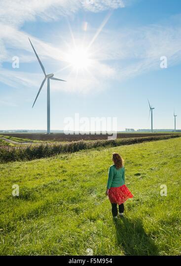 Mature woman standing in field, watching wind turbines on windfarm, rear view, Rilland, Zeeland, Netherlands - Stock Image