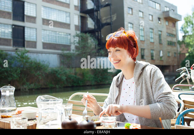 Woman having lunch by canal, East London, UK - Stock Image