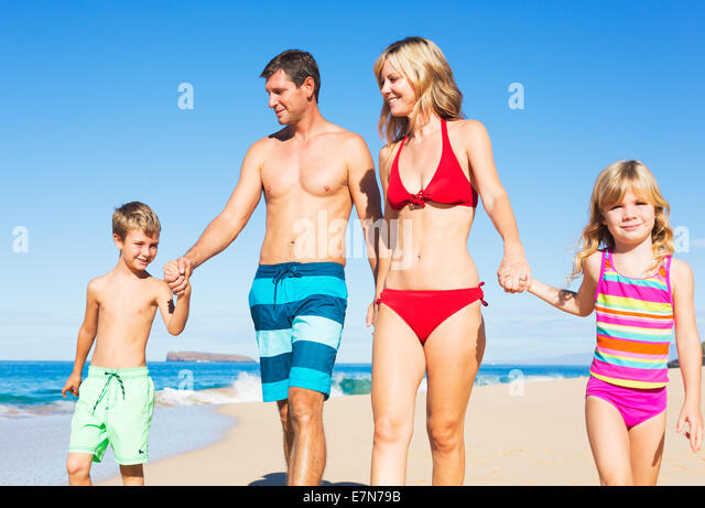 Happy Family of Four Having Fun at the Beach - Stock Image