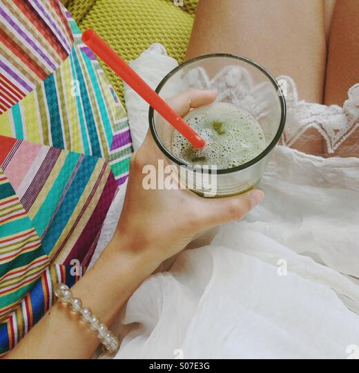 Girl's hand holding iced green tea on her lap in white dress on bright high end sofa. - Stock-Bilder