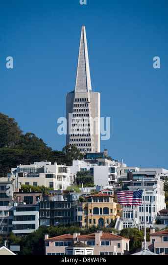 Cityscape with top of Transamerica Pyramid, houses and apartments, and a US flag in foreground, San Francisco, California - Stock Image