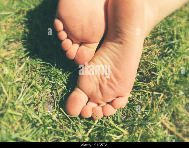 The soles of a young boy's Bare feet on fresh grass in the sun - Stock-Bilder