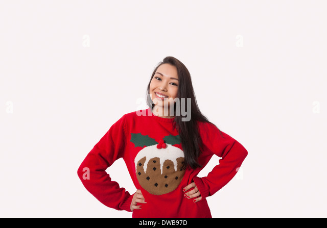 Portrait of woman in Christmas sweater standing with hands on hips over gray background - Stock Image