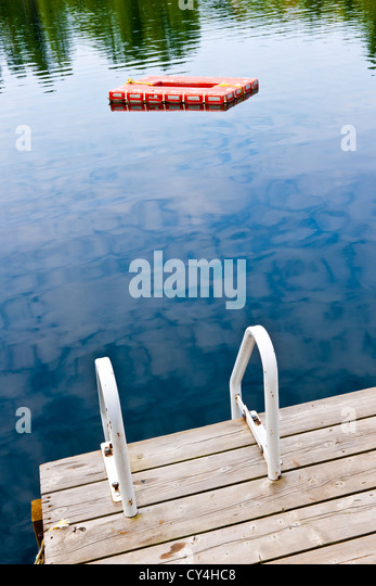Dock and ladder on summer lake with diving platform in Ontario Canada - Stock Image