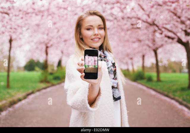 Pretty young woman showing picture of spring blossom garden while standing at a park. Caucasian young female showing - Stock Image