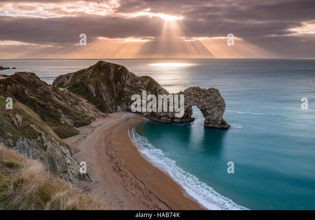 Lulworth, Dorset, UK.  28th November 2016.  UK Weather.  Beams of sunlight shine through breaks in the thinning - Stock Image