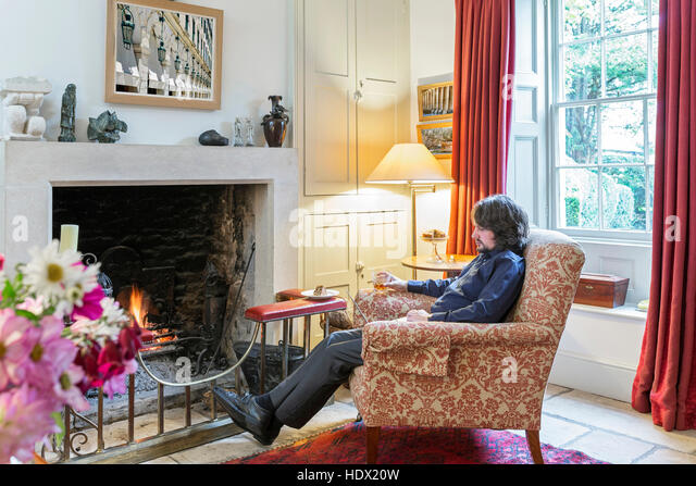 Caucasian man sitting in armchair near fireplace drinking cocktail - Stock Image