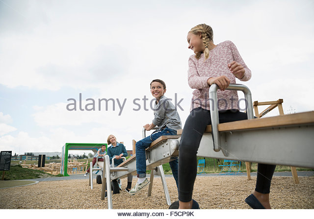 Kids playing on long seesaw at playground - Stock Image